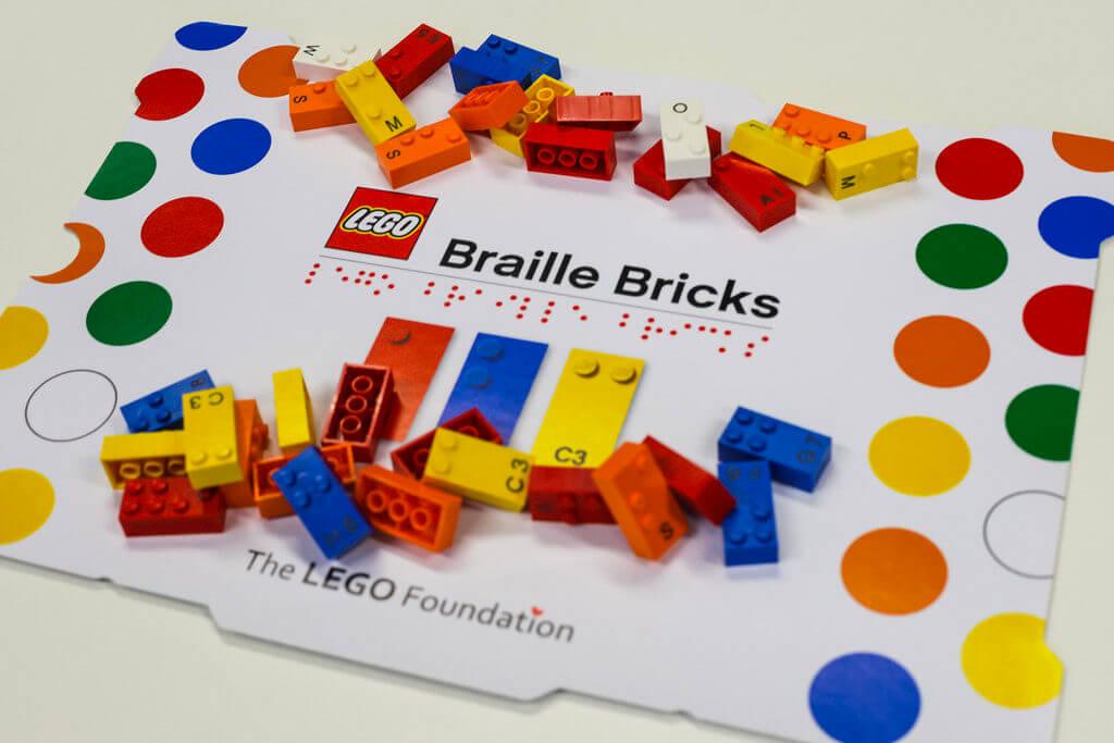 Coperchio della scatola LEGO Braille, con su scritto Braille Bricks in caratteri latini e Braille. Alcuni mattoncini colorati con sia scrittura Braille e latina.