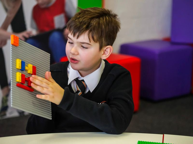 Bambino non vedente tocca i mattoncini LEGO Braille.