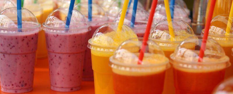 frullati di frutta in bicchieri di plastica con cannucce di plastica