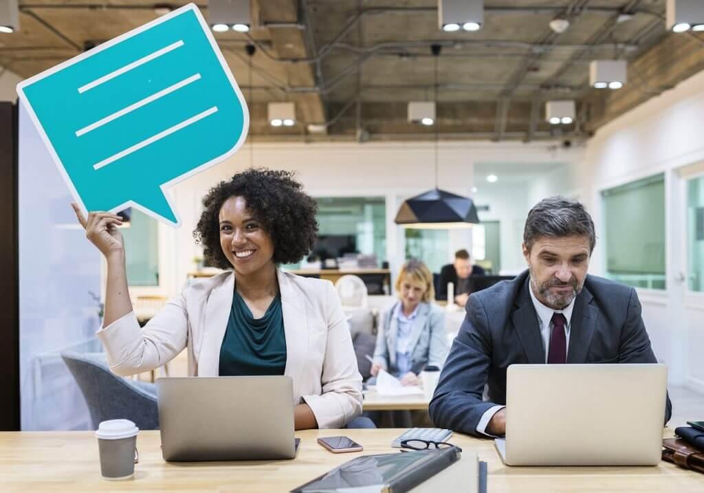 persone sorridenti in ufficio con cartello a forma di fumetto
