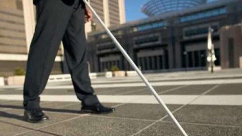 Fotografia delle gambe di una persona cieca con un bastone per orientarsi nella piazza di una città.